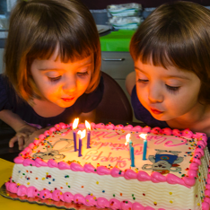 two girls with a birthday cake